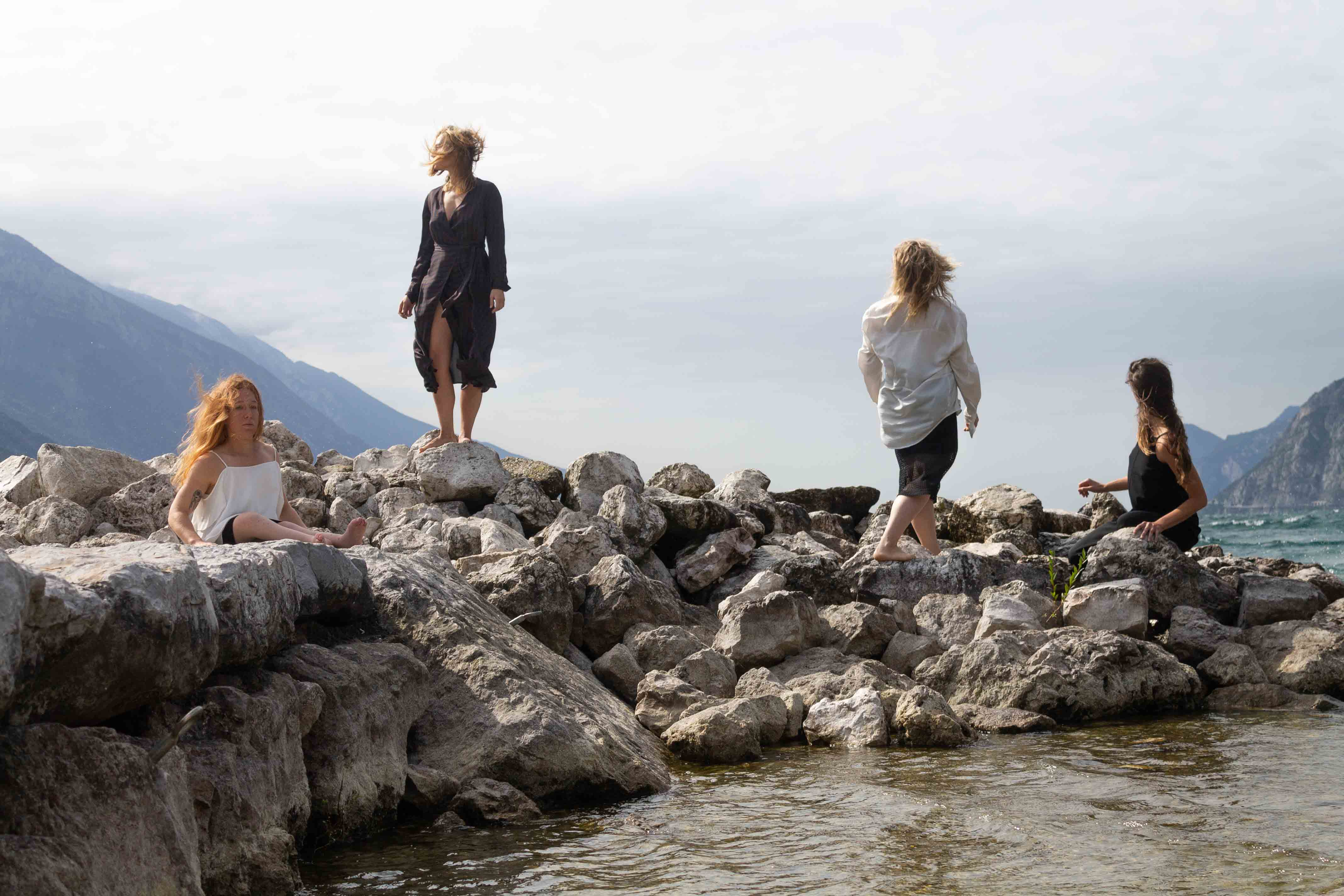 The image depicts four dancers wearing billowing clothes, standing and sitting on a pile of rocks at Lake Garda in northern Italy. In the background we see mountains sloping towards the lake. Photo: Federico Gazza