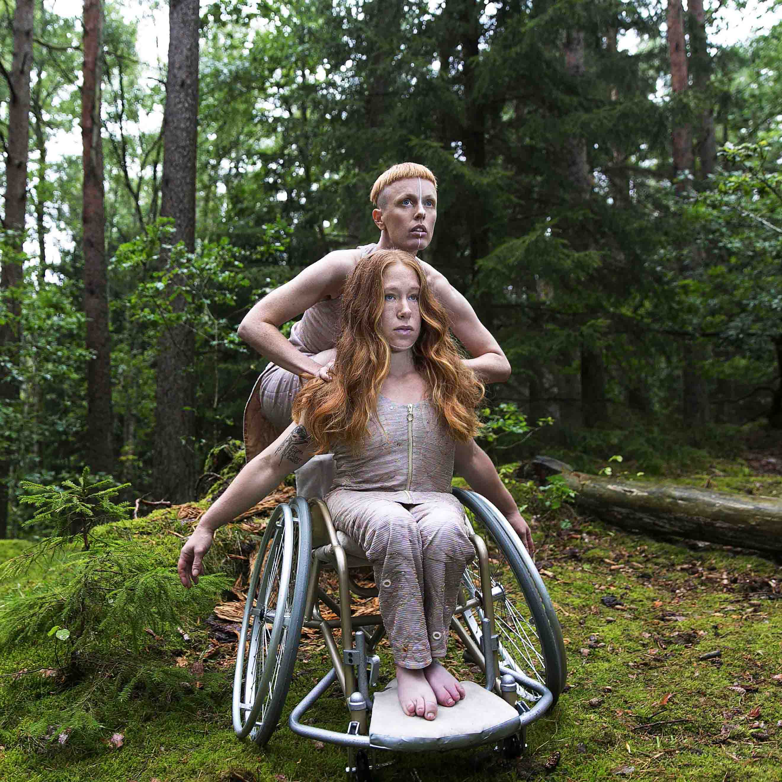 Image for the performance Hannah Felicia. The image depicts the dancers in a forest, wearing costumes shimmering in pink. Felicia is sitting in a wheelchair with her arms pointing backwards, flowing red hair, looking upwards right. Behind her, up on the wheelchair, Hannah crouches, also looking upwards right. Photo: Anna Ósk Erlingsdóttir