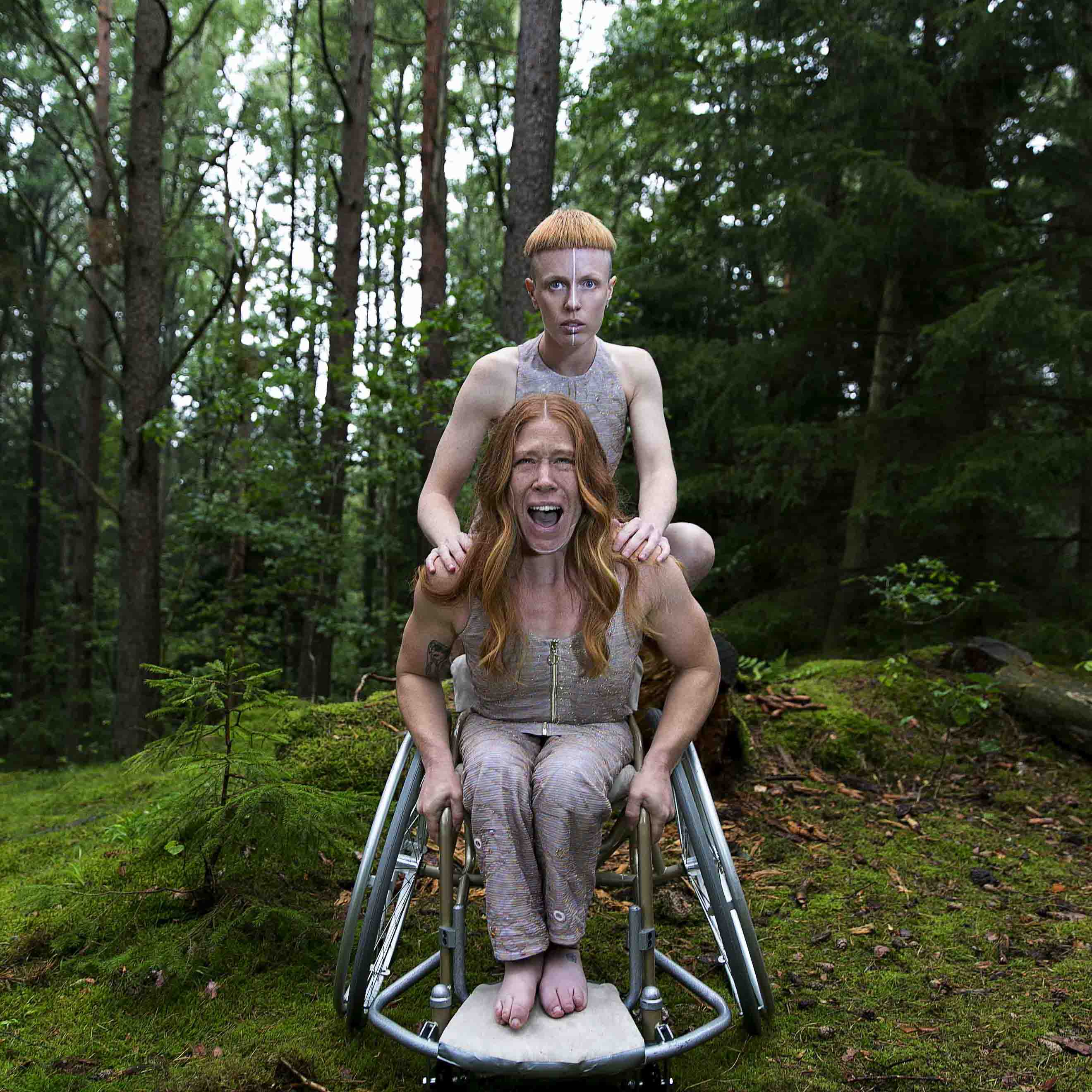 Image for the performance Hannah Felicia. The image depicts the dances in a forest, wearing costumes shimmering in pink. Felicia is sitting in a wheelchair with her arms on the wheels, with flowing red hair she screams directly into the camera. Hannah is crouched behind Felicia on the wheelchair, looking straight into the camera. Photo: Anna Ósk Erlingsdóttir