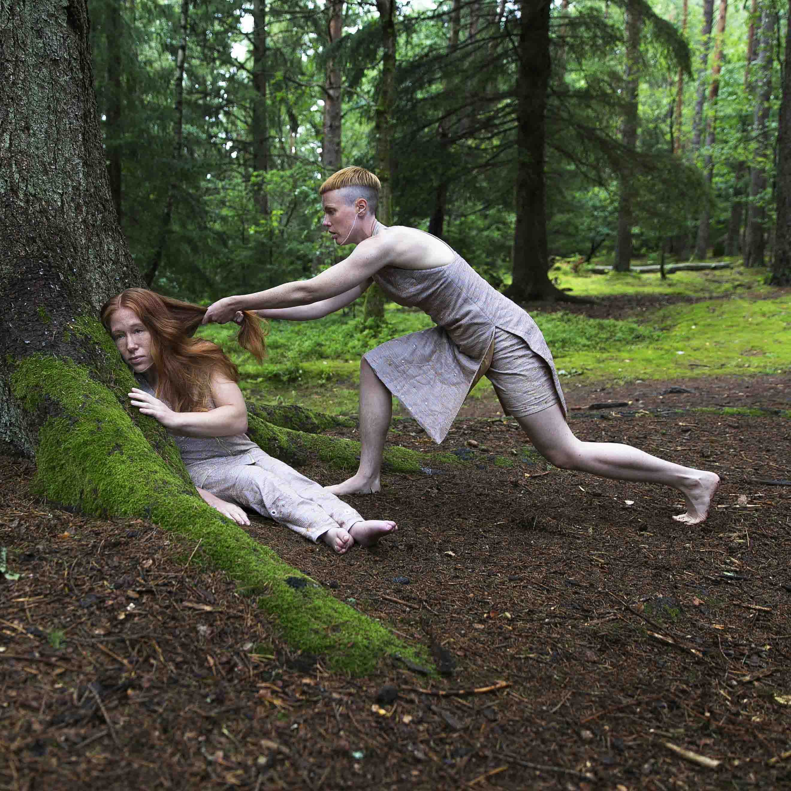 Image for the performance Hannah Felicia. The image depicts Felicia sitting leaning towards a tree in a fir forest, gazing far-off to the left, while Hannah stands in profile with her left leg vigorously arched backwards, looking directly at Felicia while pulling her hair. Photo: Anna Ósk Erlingsdóttir