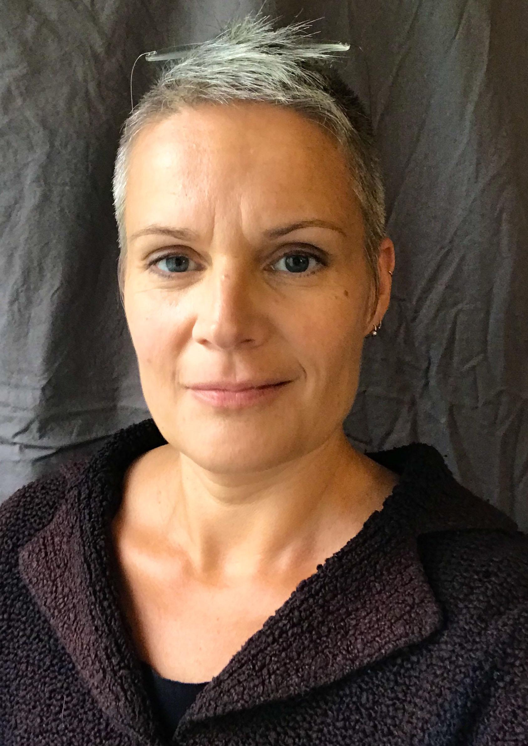 Porträttbild av kostymdesignern Charlotte von Weissenberg. Hon står mot en grå bakgrund i tyg med ljus från vänster och tittar in i kameran, med kortklippt hår och mörklila kofta.