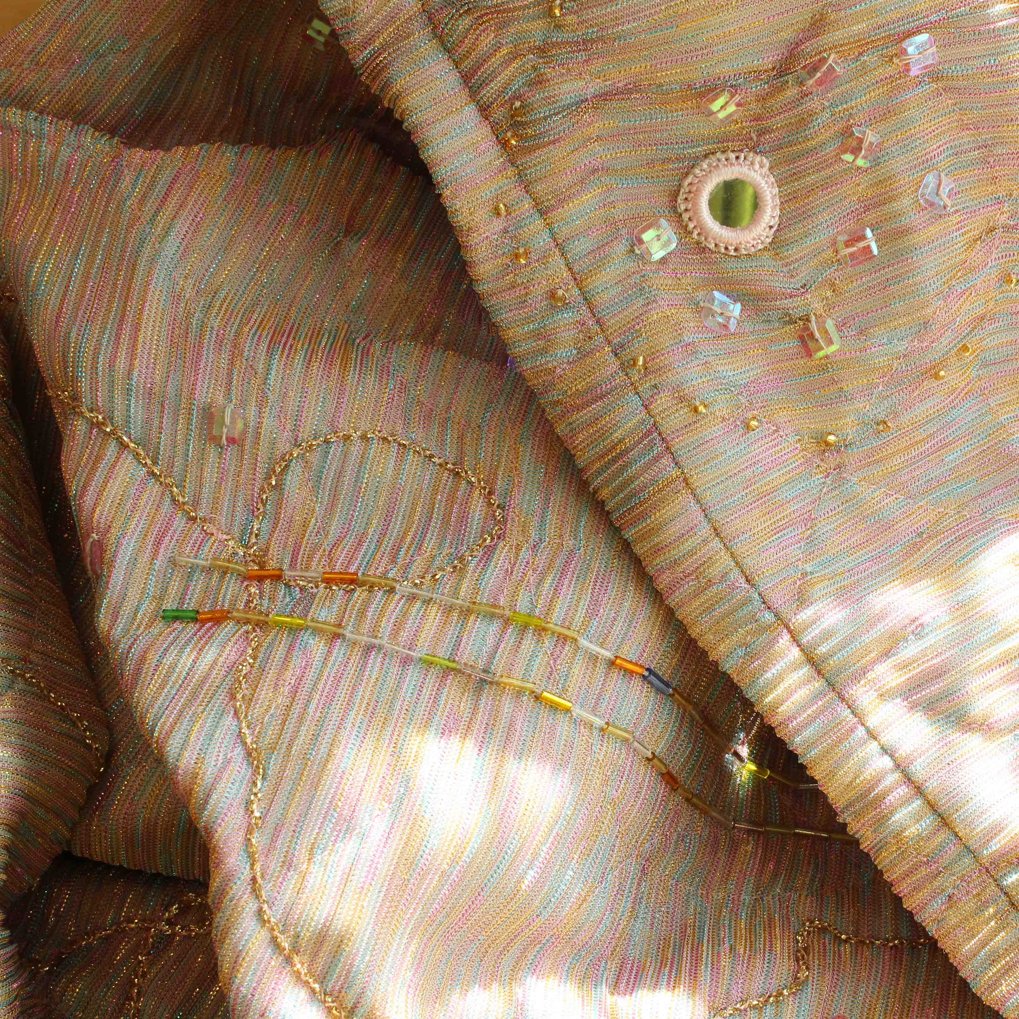 Close-up of the costume. The image depicts the fabric that glitters in pink, yellow, light blue and silver, with details like embroideries, pearls and buttons.