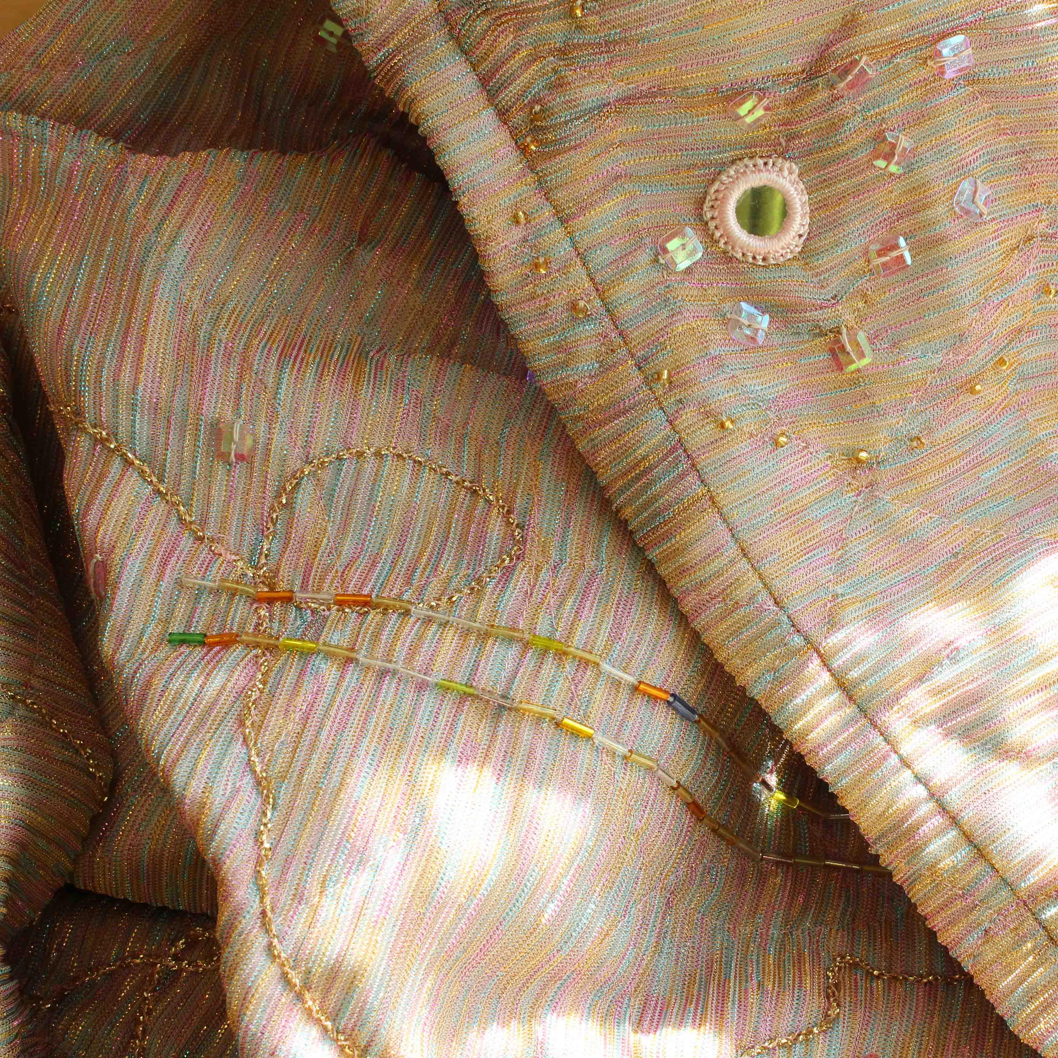 Närbild på kostymen. På bilden ser vi tyget som glittrar i rosa, gult, ljusblått och silver, med detaljer som broderier, pärlor och knappar.