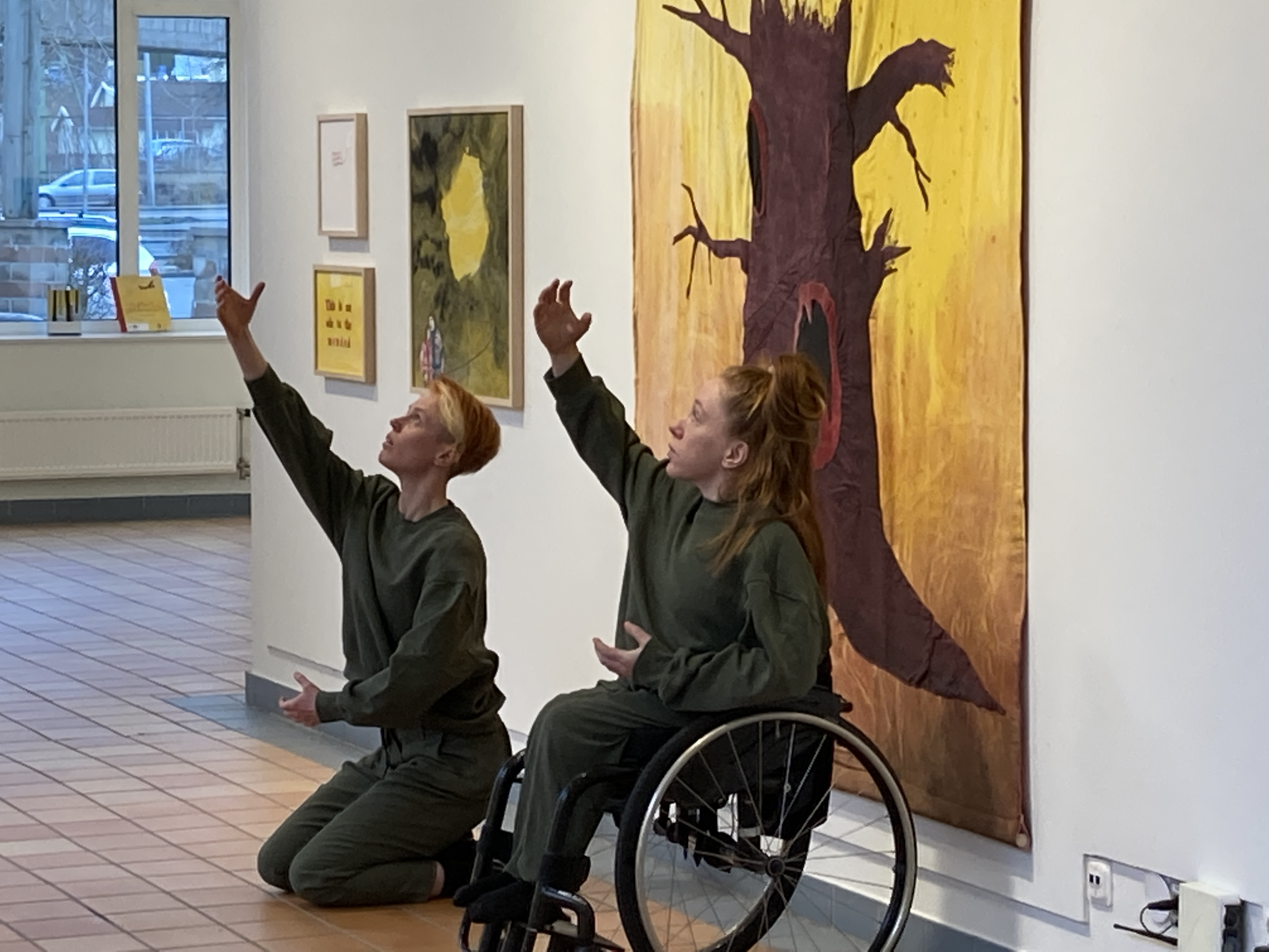 The image depicts dancers Hannah Karlsson and Felicia Sparrström wearing dark green clothes, sitting in front of a painting depicting a tree. The dancers are looking towards the top left corner of the picture, while stretching out their right arms in the same direction. Photo: Veera Suvalo Grimberg