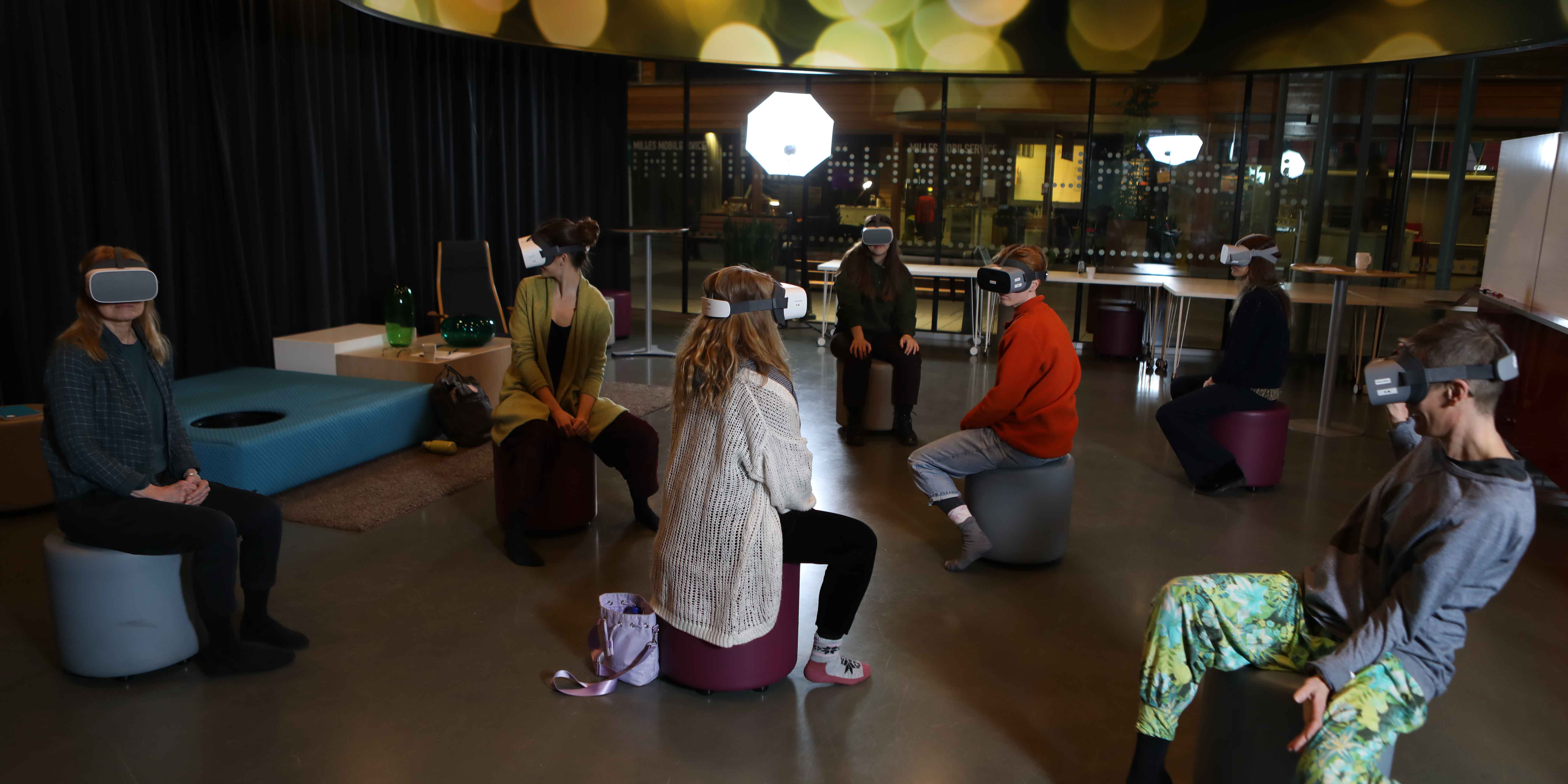 The image shows seven people sitting on fabric-covered stools in a dimly lit room. They are all wearing mask resembling binoculars. Photo: GGM FIlm