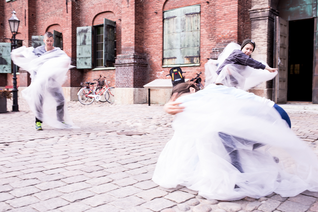 The image depicts the dancers wearing grey clothes, wrapped in white billowing fabric. In the background is a brick building, the ground is paved with stone.