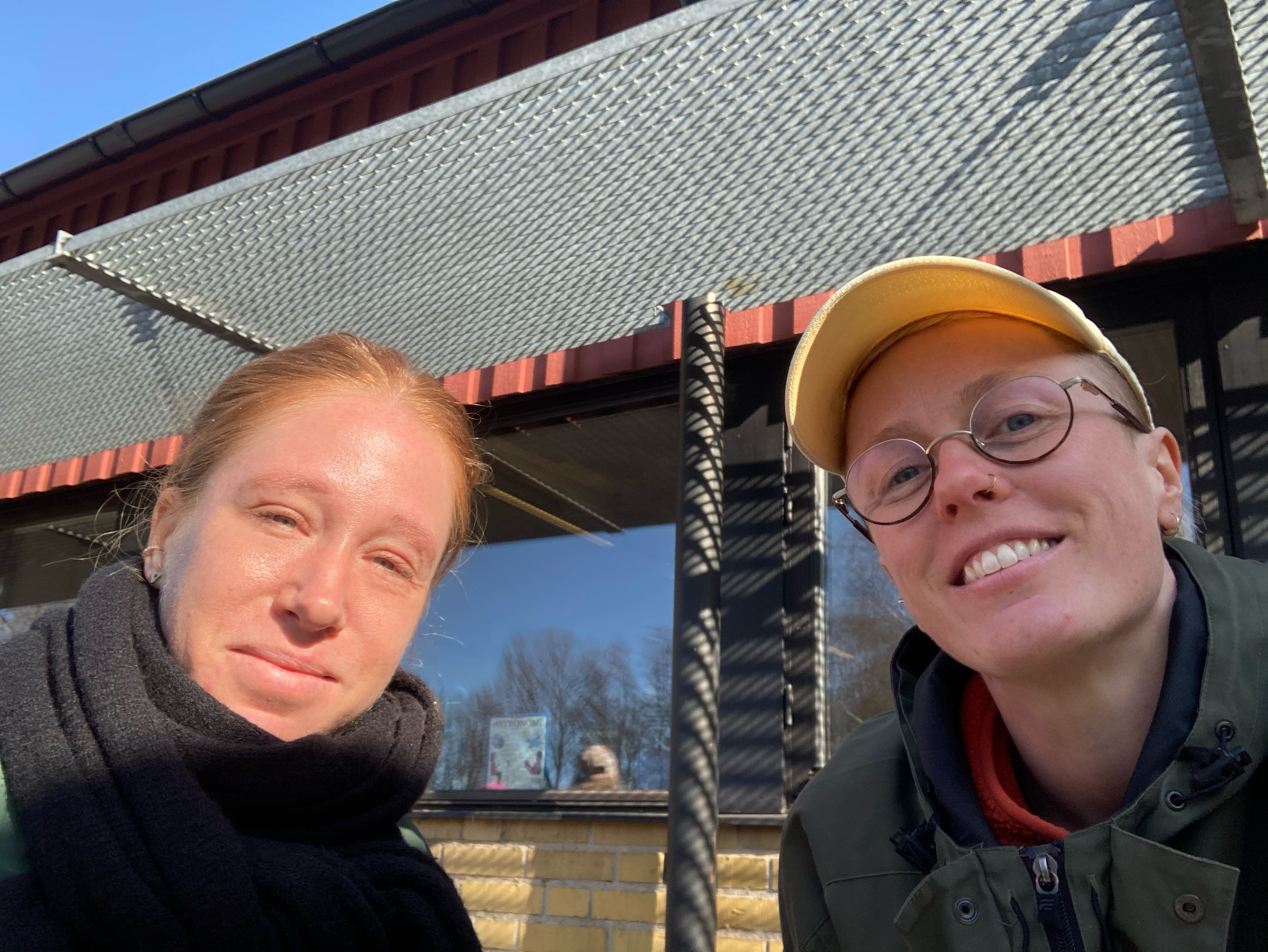 The image shows dancers Felicia Sparrström and Hannah Karlsson. Felicia on the left is wearing a thick black scarf. Hannah on the right is wearing a yellow cap and glasses.