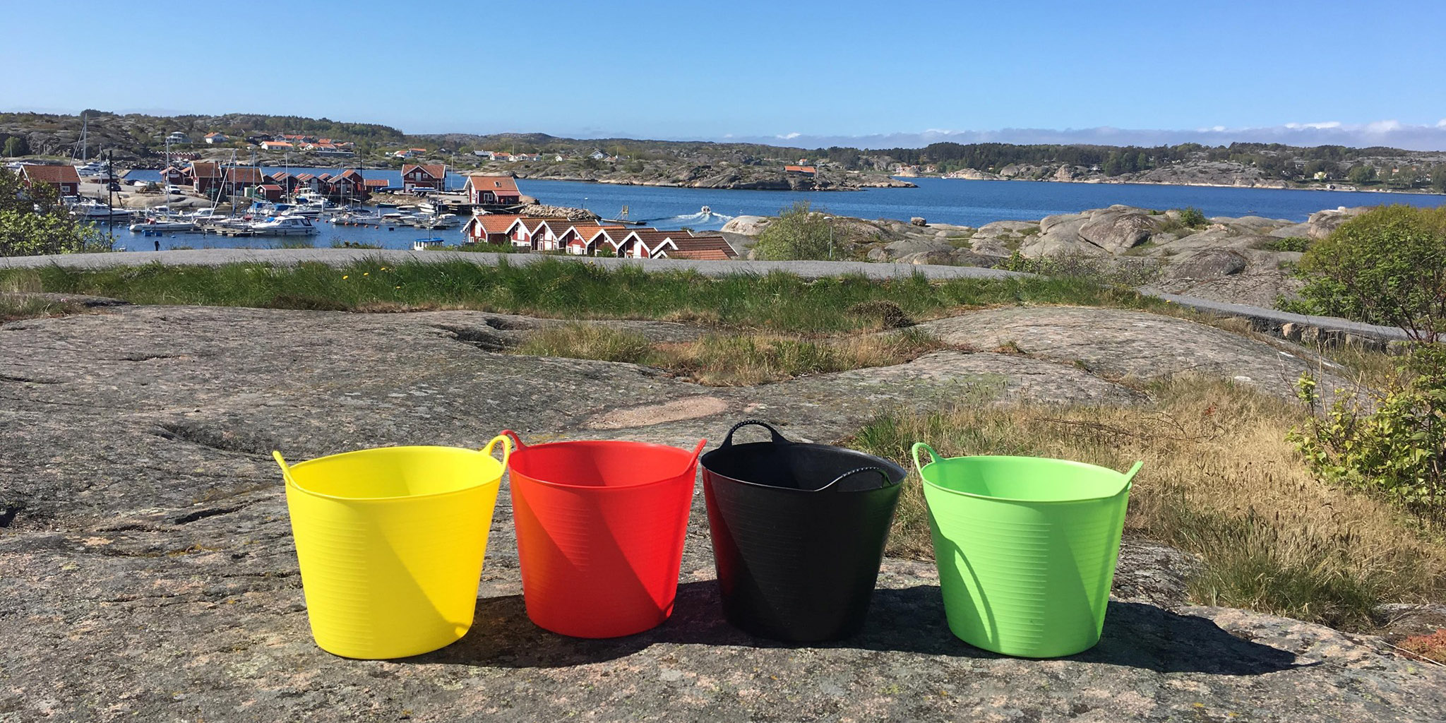 Bilden föreställer fyra stycken olikfärgade hinkar. En gul, en röd, en svart och en ljusgrön som står på en klippa. I bakgrunden ser vi små hus, båtar och havet.