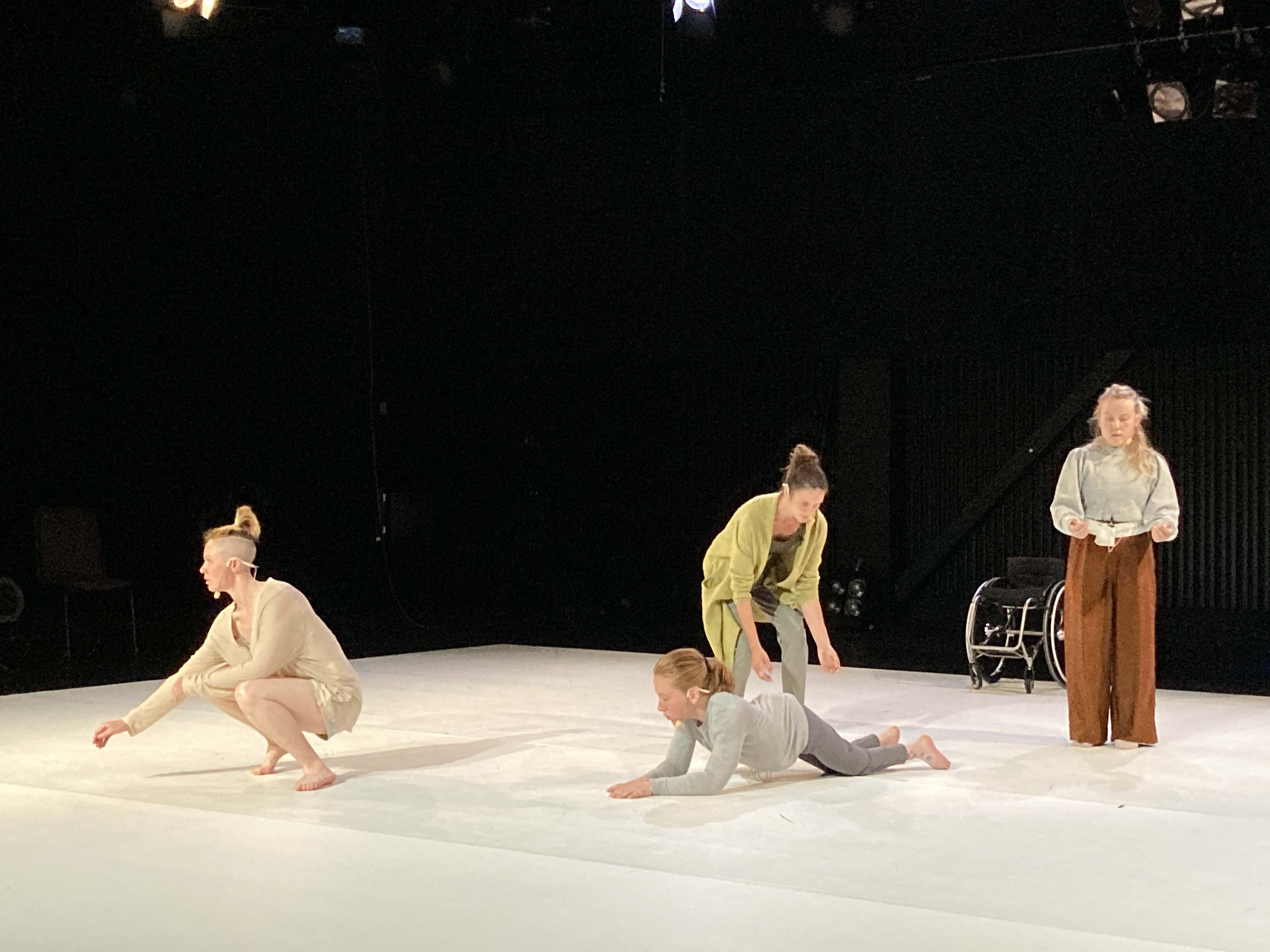 The image depicts four dancers on a white dance mat against a black background. Two of the dancers are crouching, one is on all four and one is standing up. In the background there is a wheelchair.