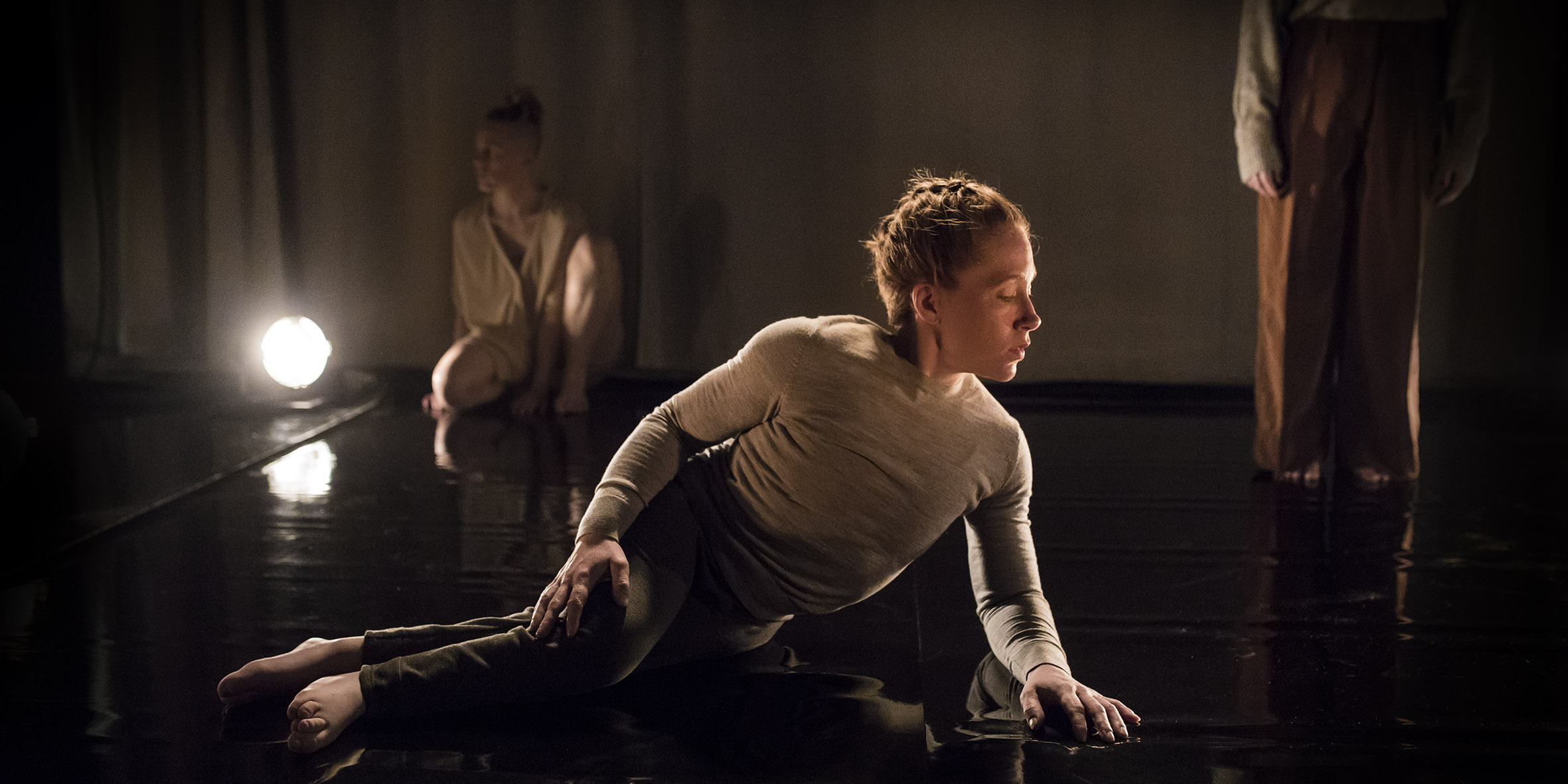 In the foreground lies a dancer with her legs to the left and her upper body to the right. She has braided red hair and are looking down at the floor. In the background to the left sits a dance out of focus next to a bright spotlight. In the background to the right we see the legs and parts of the arms of a person. The picture is dark and light is reflected on the shiny floor. Photo: Polina Ulianova
