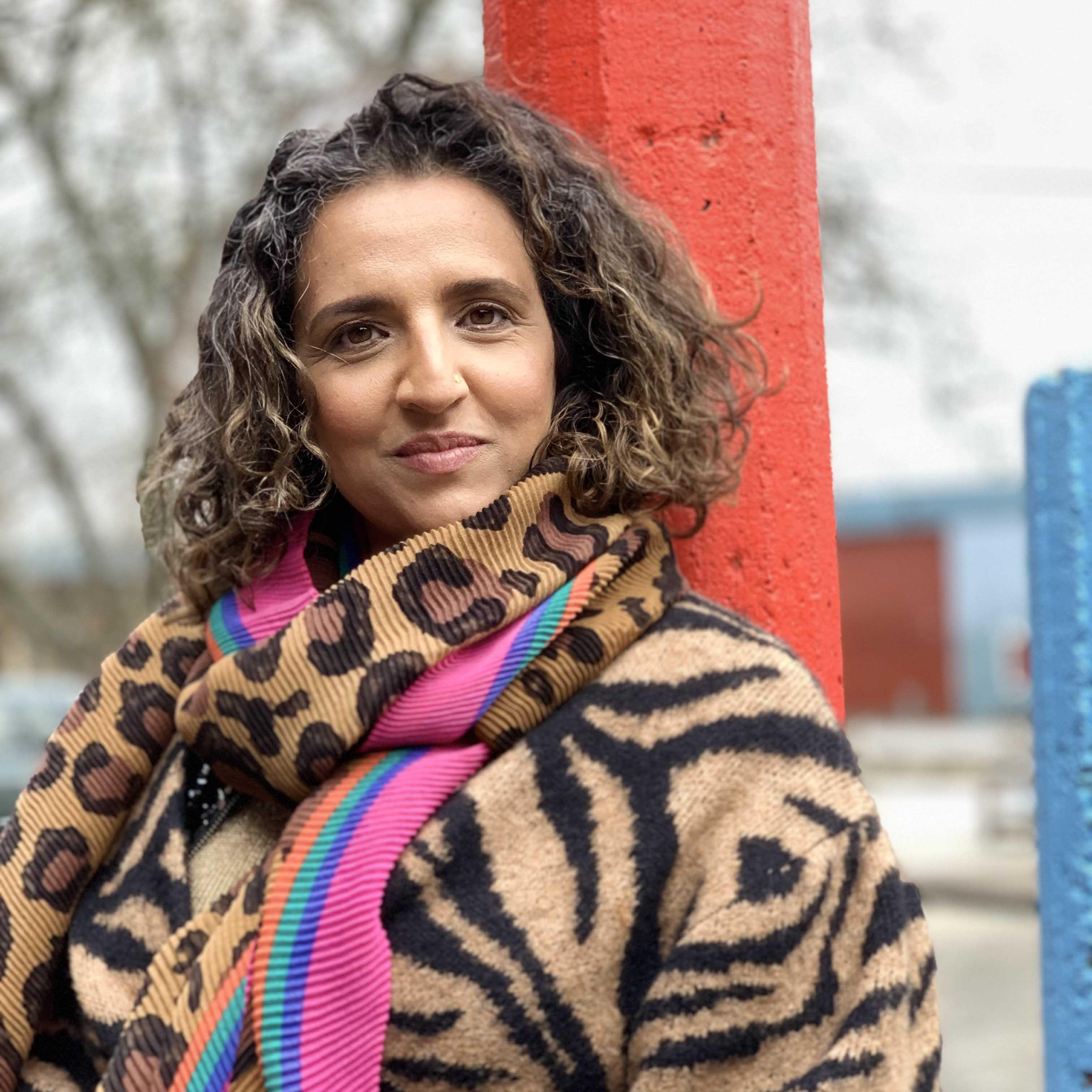 Bilden är ett porträtt i halvfigur av dansaren och koreografen Rani Nair. Rani har lockigt brunt hår och tittar rakt in i kameran. På sig har hon en tigermönstrad kappa, en leopardmönstrad halsduk och ytterligare en färgglad halsduk i rosa, orange, lila och ljusblått.